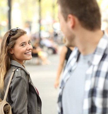 man and woman smile at each other on the street demonstrating places to meet women