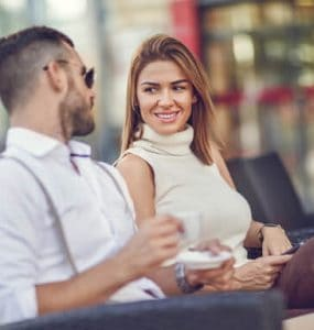 attracting women man and woman sitting and talking, creating rapport and an emotional connection