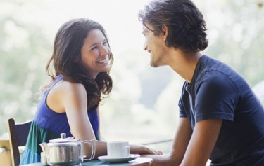 guy talking to smiling girl at table